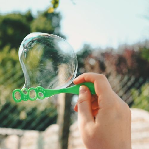 Cropped image of person holding bubbles