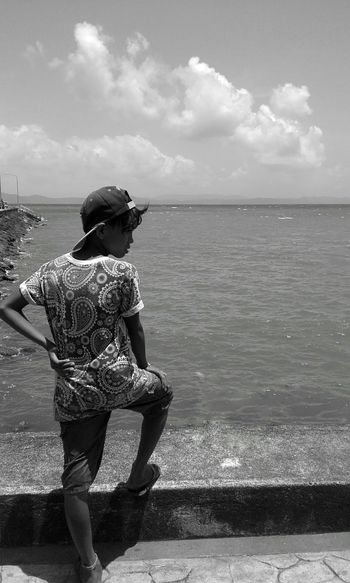 Rear View Of Teenage Boy Standing On Retaining Wall Against Sea