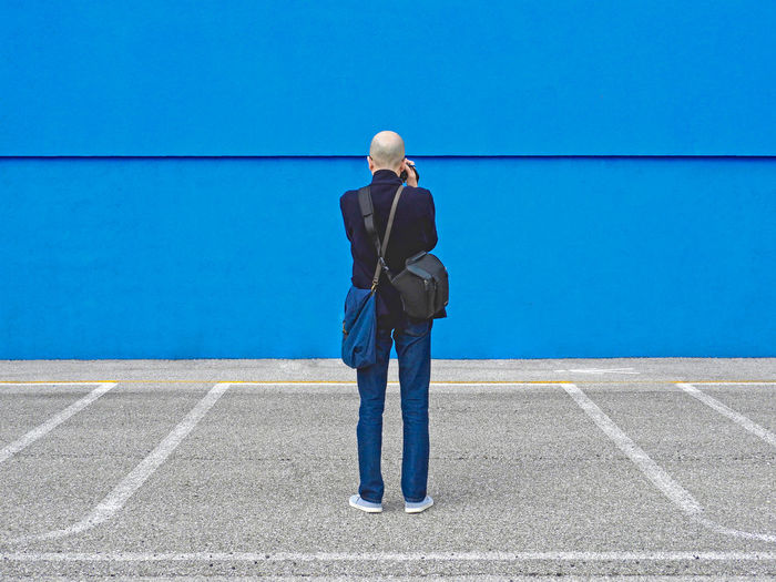 Rear View Of Man Photographing Blue Wall On Road In City