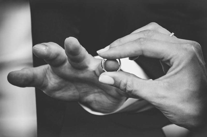 Cropped image of bride exchanging ring with groom during wedding