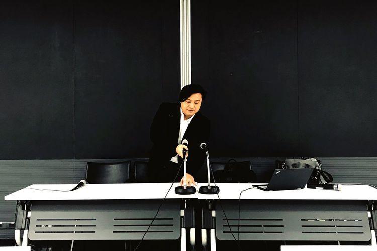 Businessman adjusting microphone in seminar