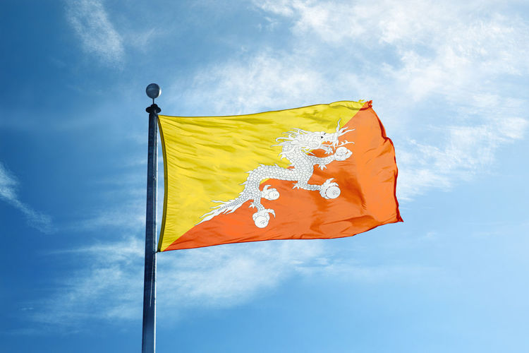 Low angle view of bhutan flag against blue sky