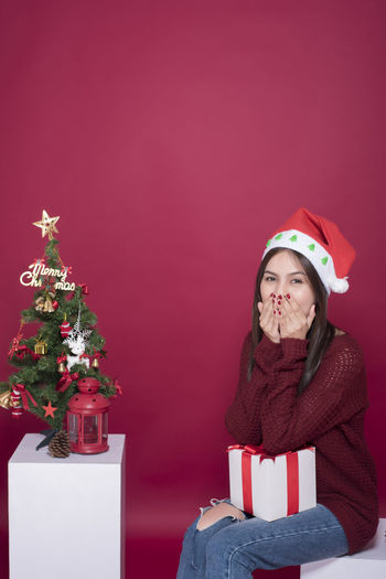 Portrait Of Young Woman With Christmas Decoration And Present Against Maroon Background