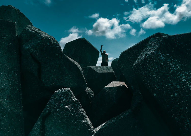 Rear view of man standing on rocks against sky