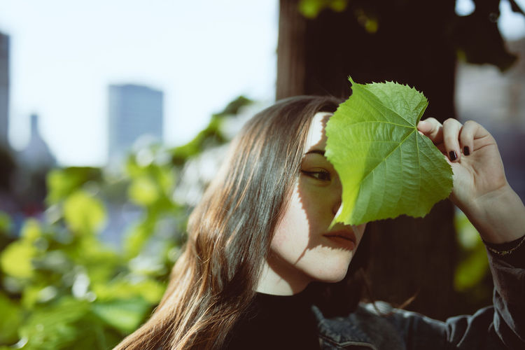 Close-up of smiling young woman covering face with leaf