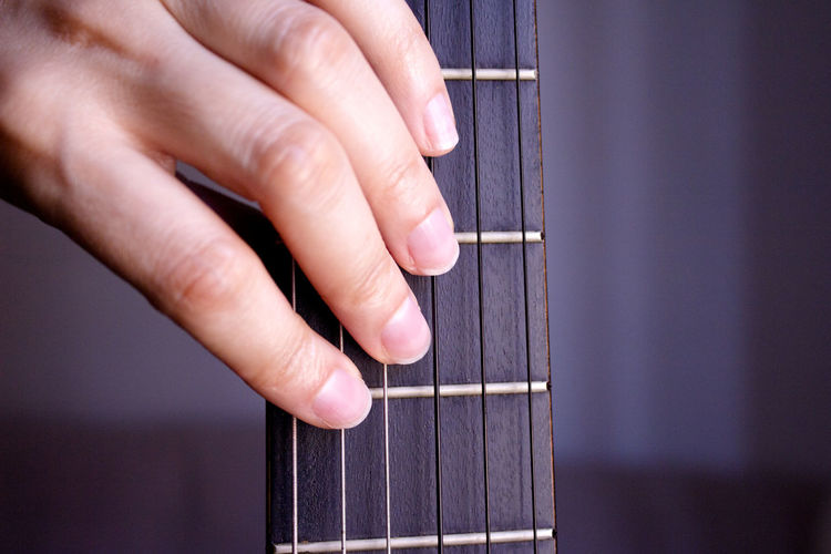 Close-up of hands touching guitar