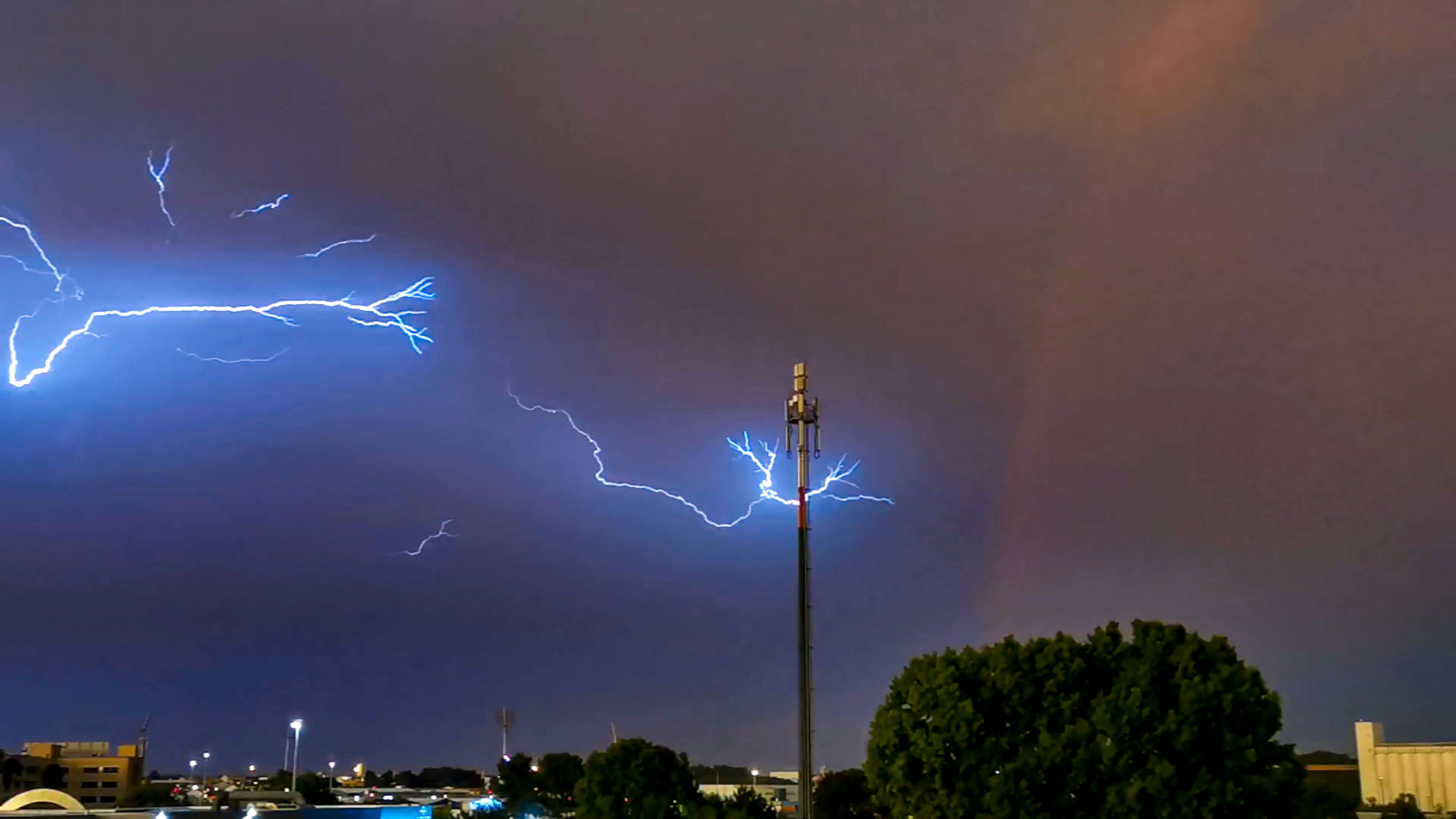 lightning, power in nature, storm, thunderstorm, cloud, thunder, sky, beauty in nature, forked lightning, night, electricity, warning sign, storm cloud, sign, environment, dramatic sky, communication, nature, architecture, extreme weather, tree, building exterior, illuminated, city, rain, no people, bolt, outdoors, built structure, wet, atmospheric mood, building, overcast, violence, aggression, landscape