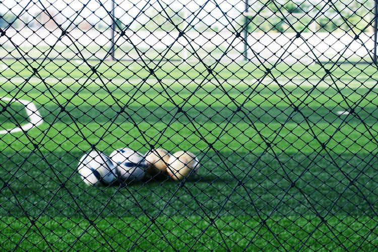 View of soccer field seen through chainlink fence