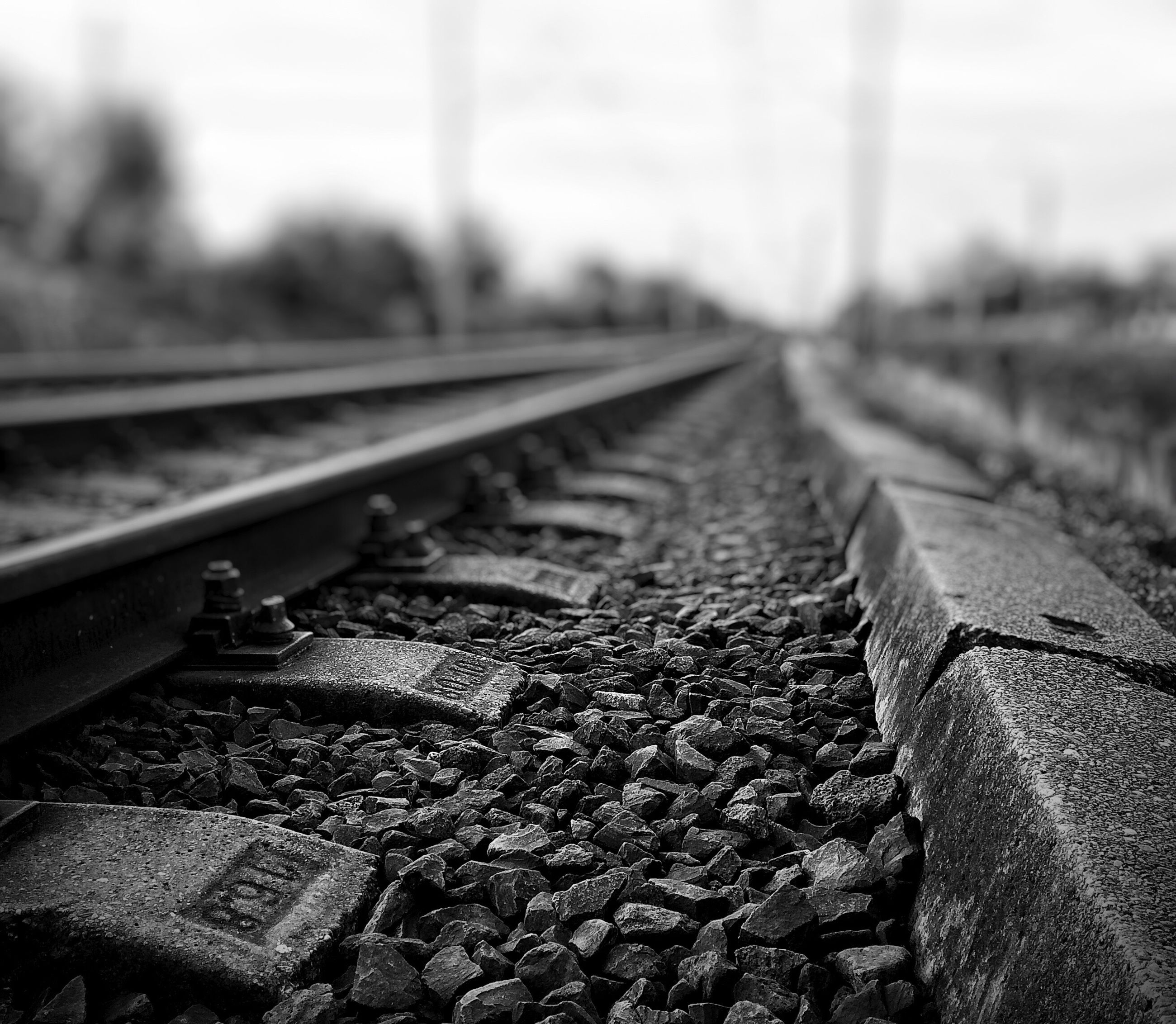 transportation, railroad track, diminishing perspective, the way forward, surface level, vanishing point, focus on foreground, selective focus, rail transportation, sky, metal, day, close-up, sunlight, one person, landscape, outdoors, road, railing, part of