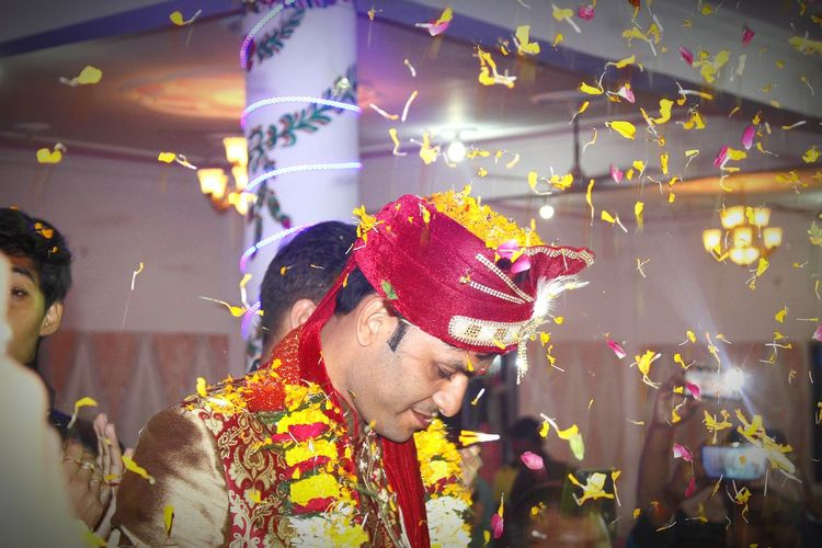 Close-up of groom amidst flowers during wedding ceremony
