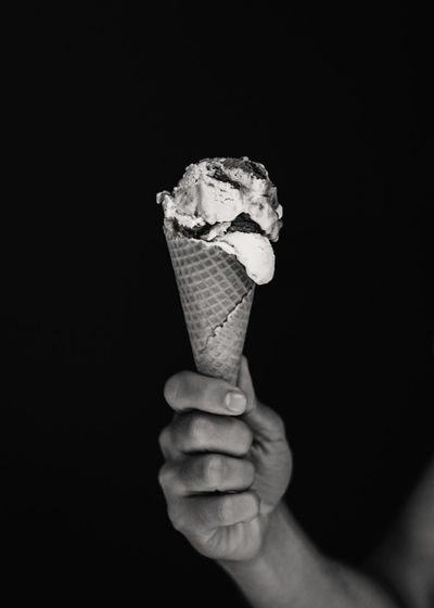 Hand holding ice cream cone against black background