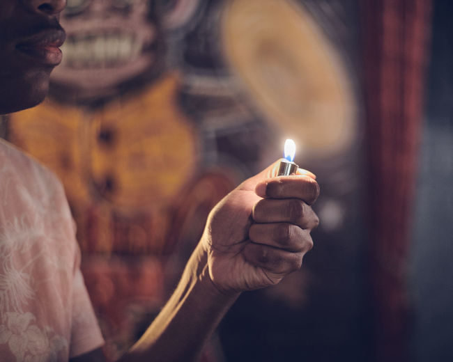 Midsection of man holding lighter