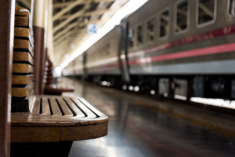 Empty wooden seat at railroad station platform