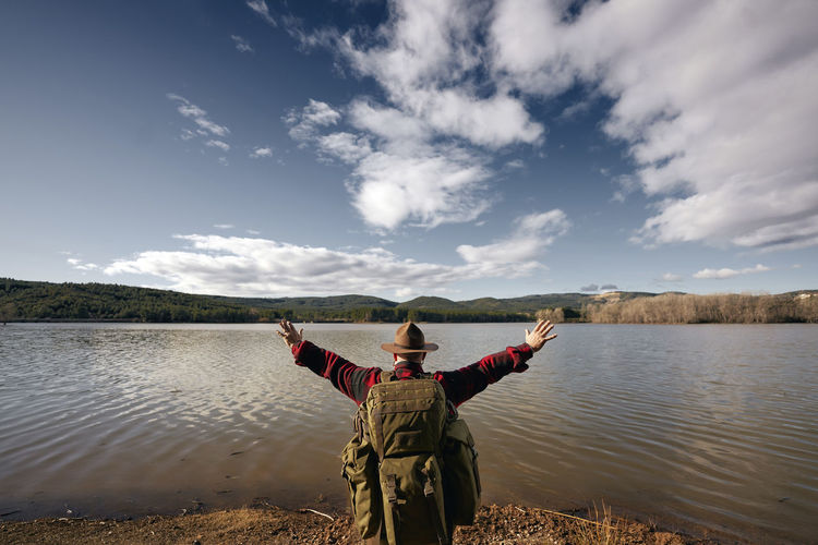 Rear view of person in lake against sky