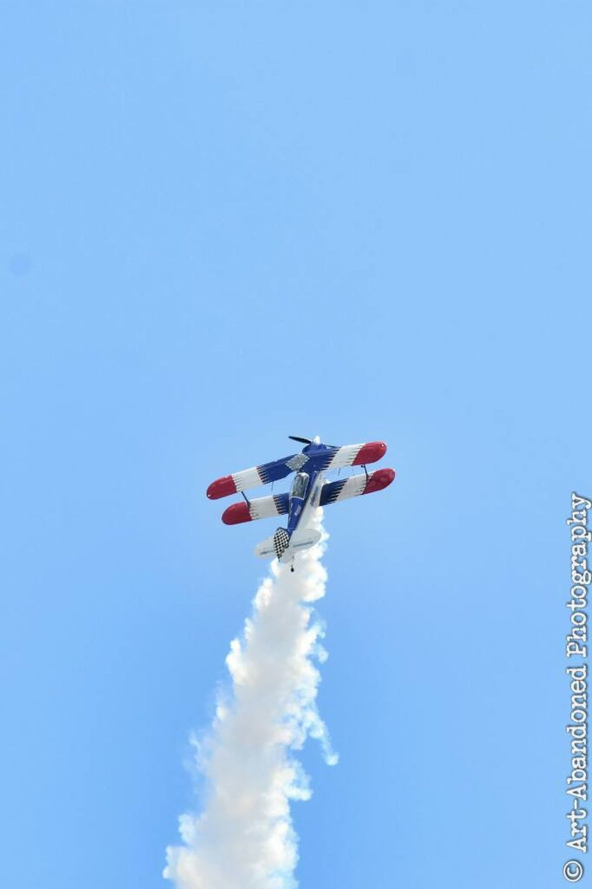 flying, low angle view, mid-air, copy space, clear sky, blue, motion, day, speed, airshow, sky, outdoors, air vehicle, airplane, multi colored, no people, parachute, vapor trail, nature, aerobatics