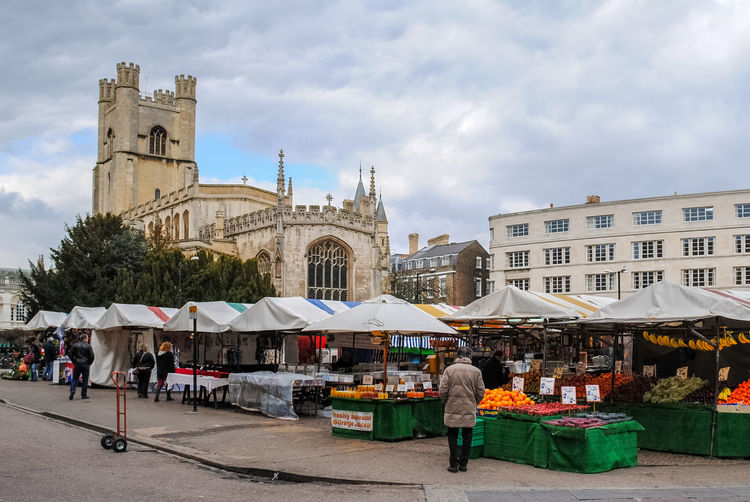 People at market stall against sky in city