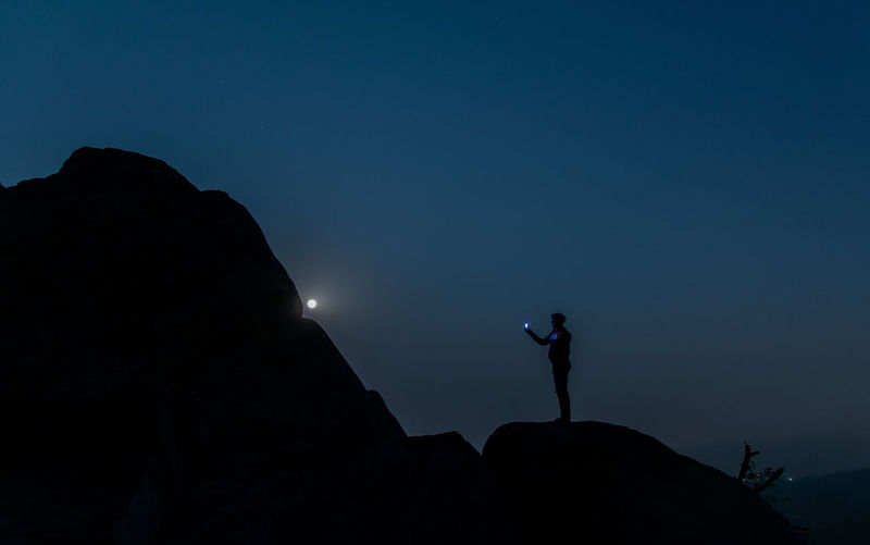 Silhouette man standing on rock against blue sky at night