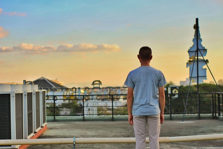 Man standing by railing in city against sky during sunset