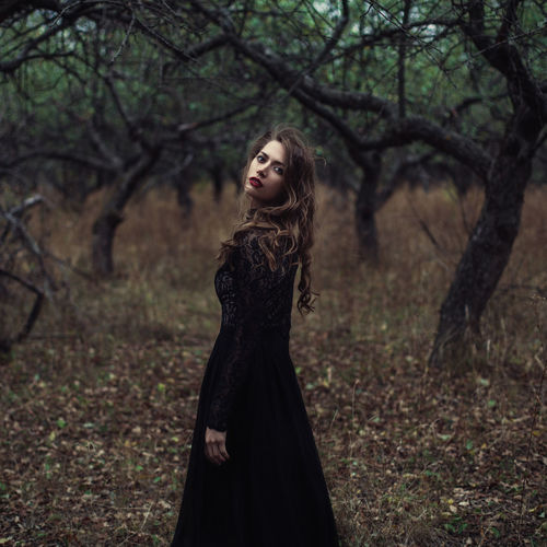 A mysterious girl in black clothes walks in a dark mystical forest. DEEP FOREST EyeEmNewHere Fairytale  Halloween Horror Mystic Whitches Night Beautiful Woman Beauty Contemplation Fashion Forest Ghotic Long Hair Mistery Mysterious Mystical Atmosphere One Person Outdoors Plant Standing Walking Whitch Women Young Women The Portraitist - 2018 EyeEm Awards
