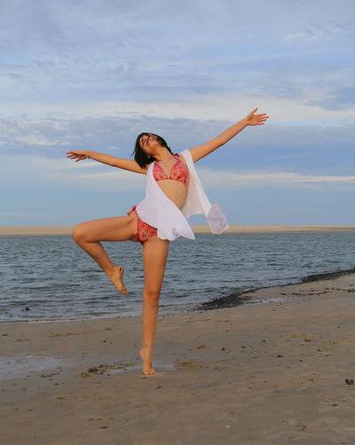 Full length of young woman in bikini dancing on beach