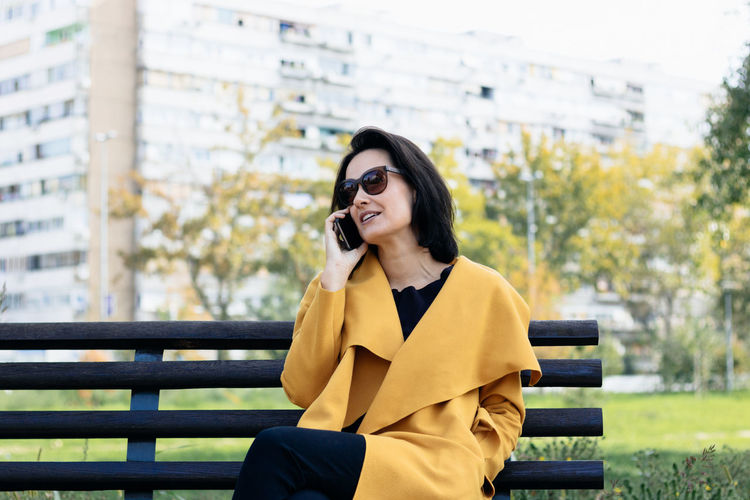 Beautiful woman talking on smart phone while sitting on public park