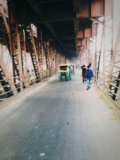 Rickshaw and people on bridge