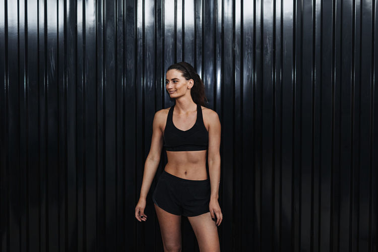 Young female athlete in sports clothing standing by corrugated iron
