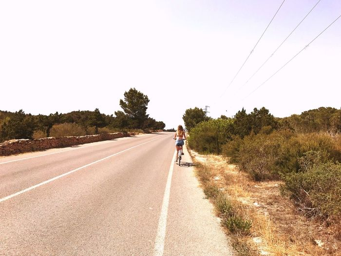 Rear view of woman riding bicycle on road against sky