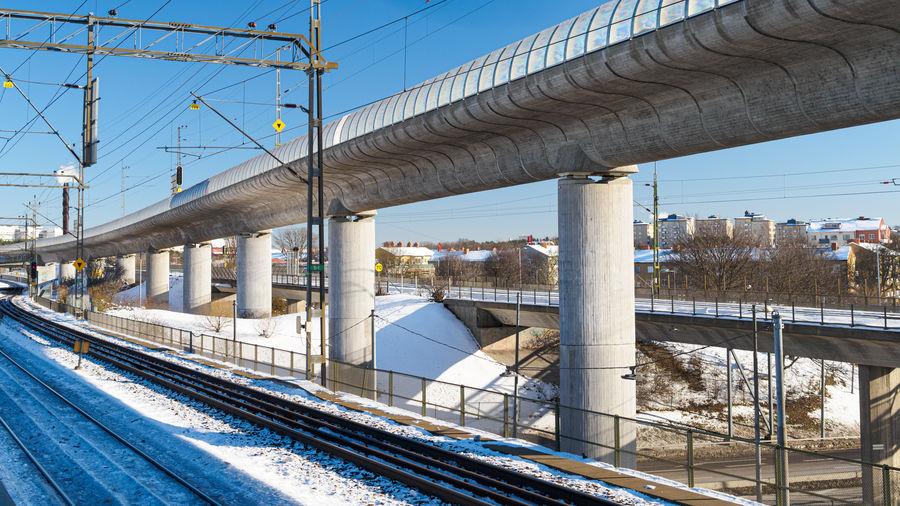 Bridge over railroad tracks against sky during winter