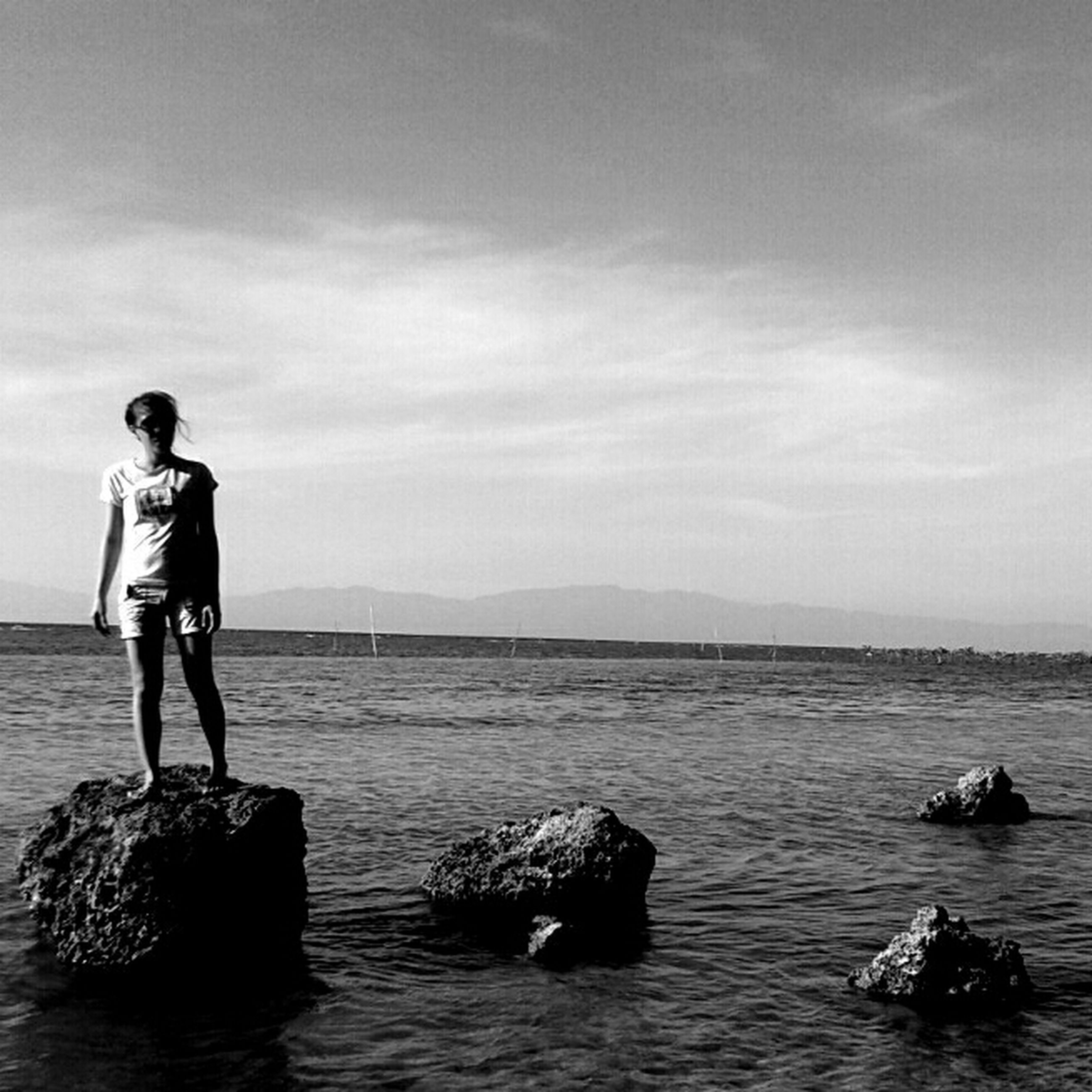 water, sea, full length, lifestyles, leisure activity, sky, horizon over water, standing, rear view, casual clothing, men, rock - object, nature, scenics, beauty in nature, tranquility, tranquil scene, cloud - sky