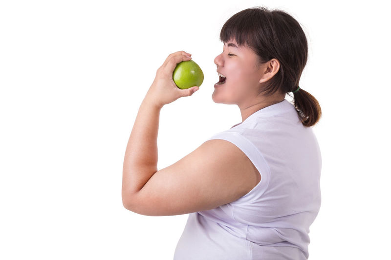 Side view of woman holding apple against white background
