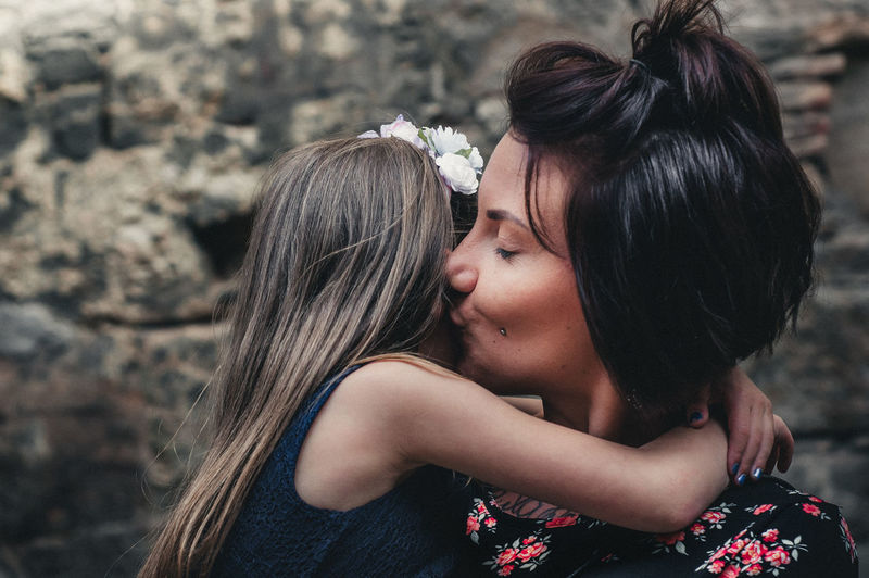 Mother kissing daughter against rock