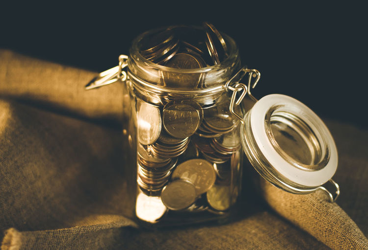 Coins In Glass Jar On Fabric