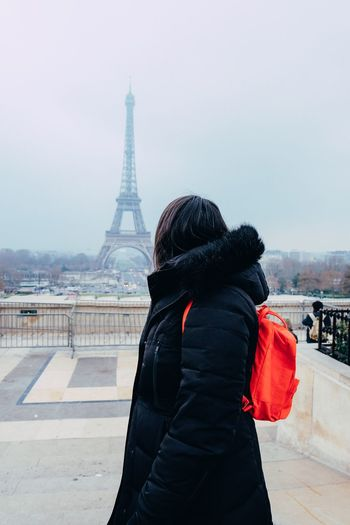 Side view of backpack woman standing against eiffel tower