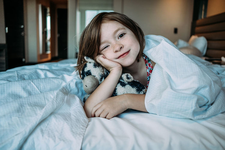 Portrait of smiling girl lying on bed at home