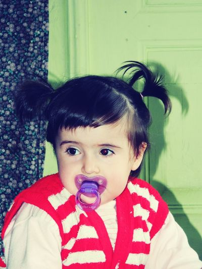 Portrait of cute baby girl with pacifier in mouth sitting by door at home