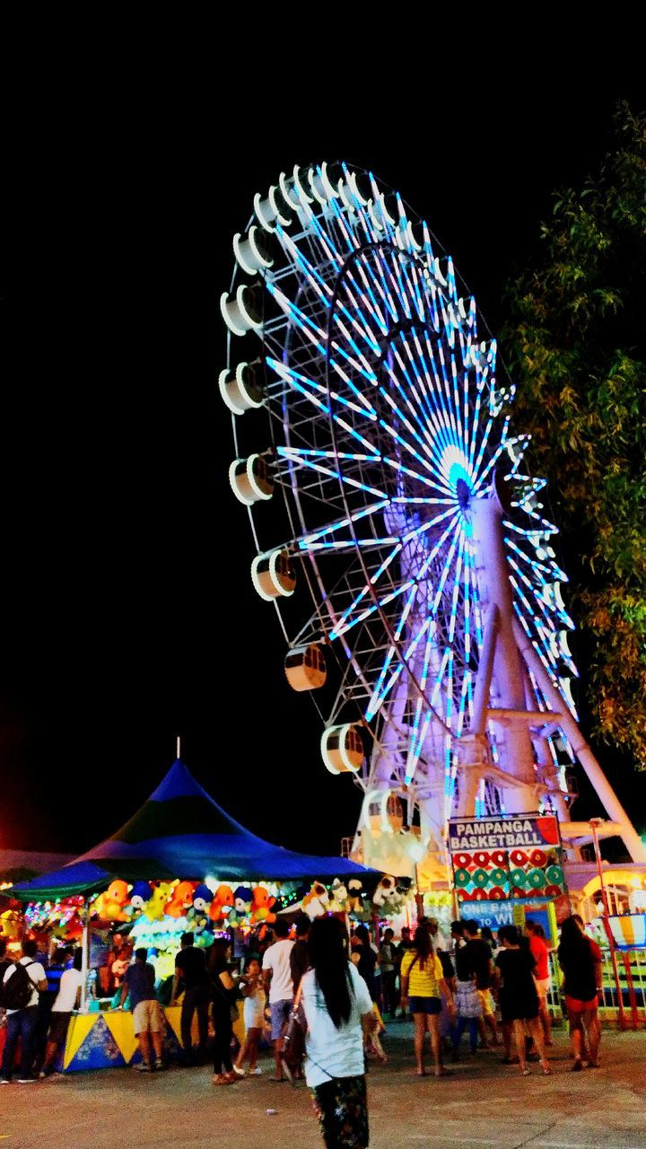 amusement park, arts culture and entertainment, leisure activity, ferris wheel, amusement park ride, enjoyment, night, illuminated, large group of people, fun, low angle view, real people, outdoors, big wheel, lifestyles, sky, people