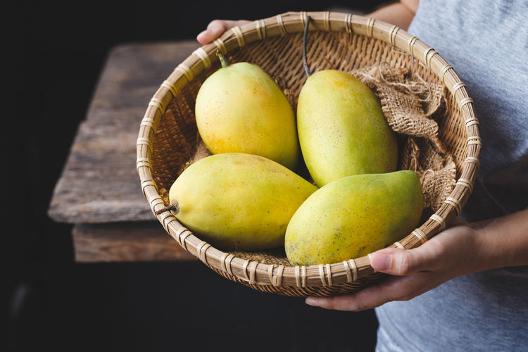 Midsection of woman holding mangoes in basket over table