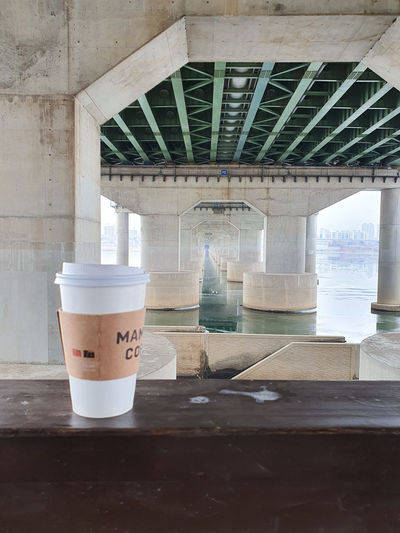 Coffee cup on table by bridge