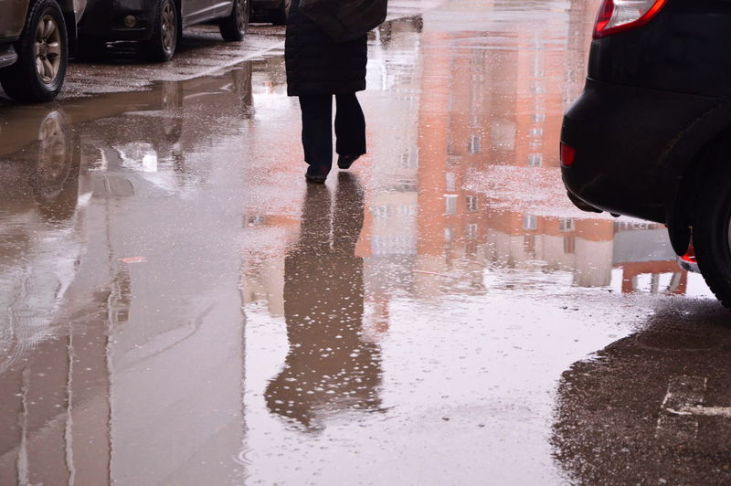 Low section of man standing on wet street in rainy season