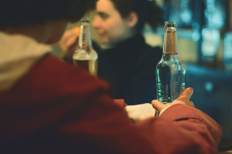 Men and woman with beer bottles in bar
