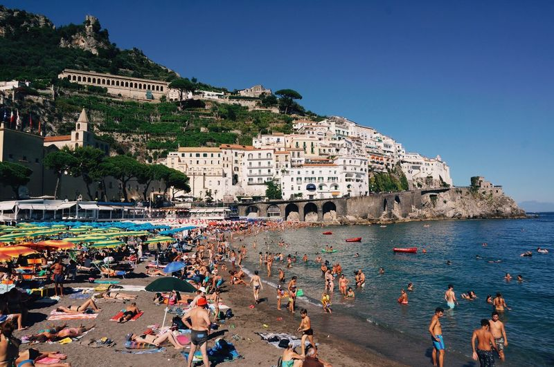 People at beach against houses in amalfi coast
