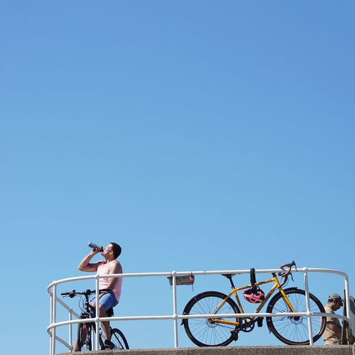 People riding bicycle against clear blue sky
