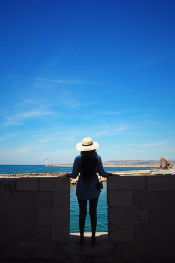 Rear View Of Woman Standing Amidst Surrounding Wall By Sea Against Sky