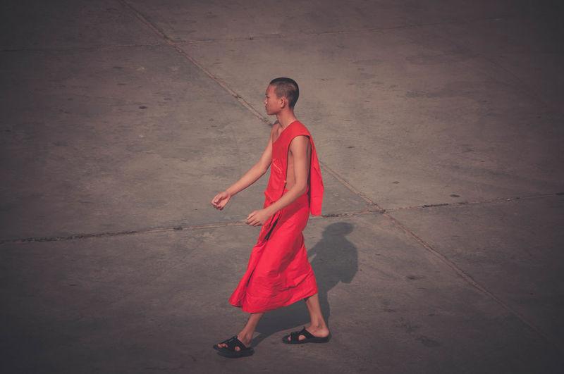 Side view of monk walking on footpath