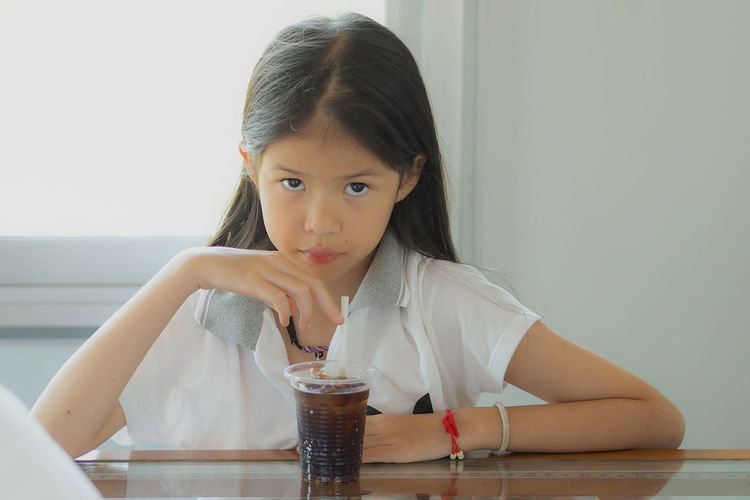 Portrait Of Girl Sitting At Table