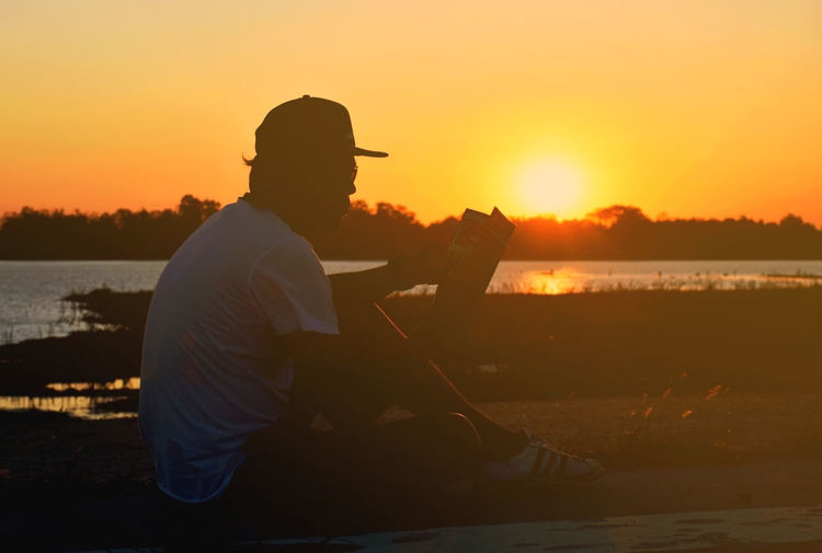 Side view of silhouette man sitting by lake against orange sky