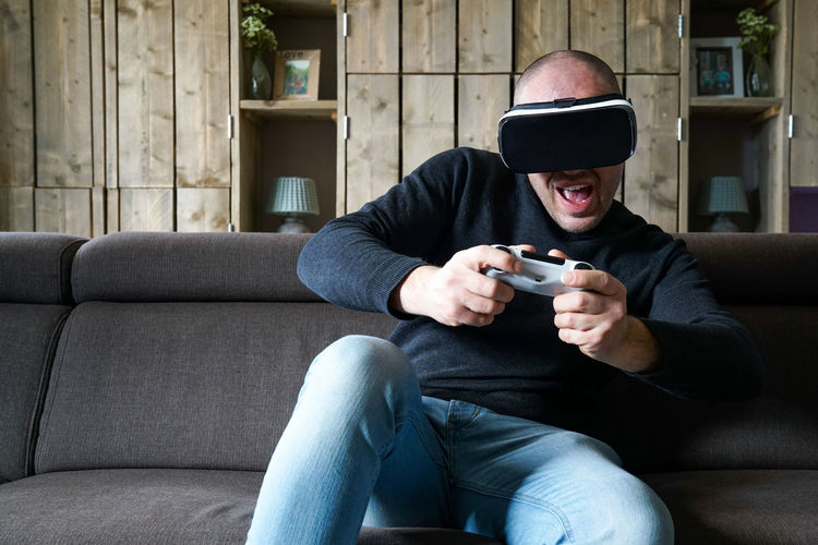 Portrait of a man having fun in the living room. Playing some games, with a virtual reality headset. Everyday futurism, smart home tech. Real People Men Sitting Relaxation Happiness Virtual Reality Furniture Gaming Smiling Technology Sofa Concept Emotion Headset Communication Adult Holding Front View Lifestyles One Person Casual Clothing Leisure Activity Wireless Technology Game Controller Three Quarter Length Indoors  Everyday Futurism Smart Home Tech