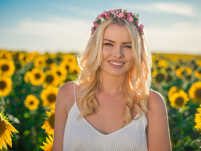 Portrait Of Smiling Woman Wearing Wreath Against Sunflower Field