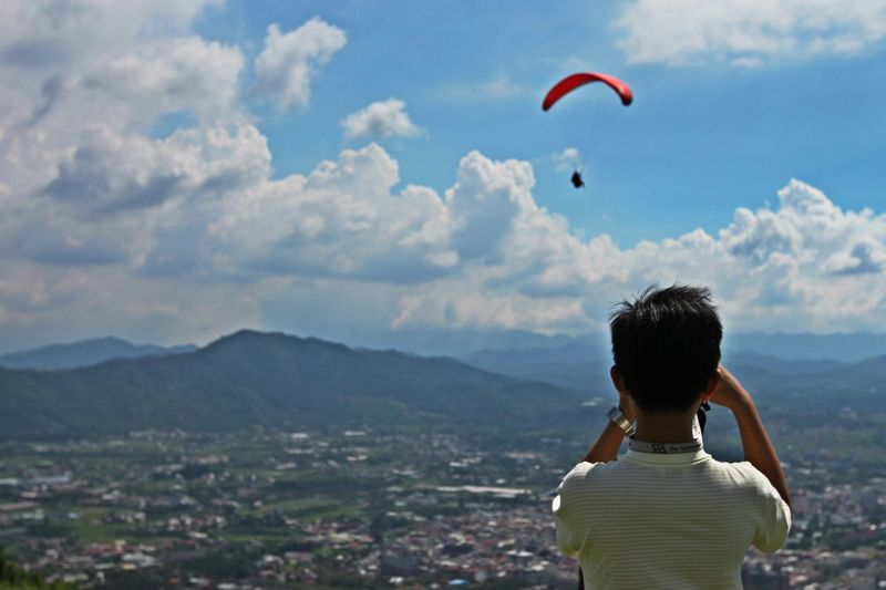 Rear view of man photographing paraglider flying over landscape against cloudy sky